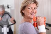 Dumbell kullanan bir spor salonunda kadın — Stok fotoğraf