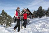 Couple trekking through snow — Stock Photo