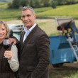 Farmer and wife in front of equipment — Stock Photo