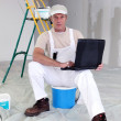 Stock Photo: Painter taking break to use his laptop