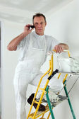 Painter making a call from top of ladder — Stock Photo