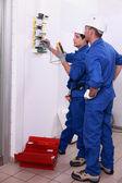 Dos electricistas inspección eléctrica, fuente de alimentación — Foto de Stock