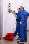 Two electricians inspecting electrical, power supply — 图库照片