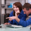Stock Photo: Two colleagues in blue jumpsuit watching a computer