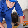 Stock Photo: Plumber preparing pipe on work bench