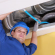 Plumber holding a blue pipe above a ceiling — Stock Photo #8319681