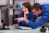 Two colleagues in blue jumpsuit watching a computer — Stock Photo