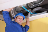 Plumber holding a blue pipe above a ceiling — Stock Photo