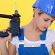 Female labourer holding drill — Stock Photo