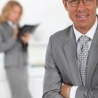 Smiling businessman in foreground — Stock Photo