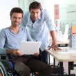 Man in wheelchair holding laptop computer next to colleague — Stock Photo