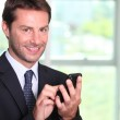 Businessman texting on a mobile phone — Stock Photo #8320909