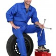Mechanic with tyre and tools - Stock Photo