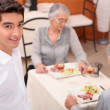 Mature couple and young waiter at restaurant — Stock Photo