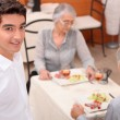 Mature couple and young waiter at restaurant — Stock Photo #8321416