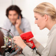 Stock Photo: TV repairwomwith soldering gun