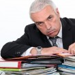 Man leaning on paperwork - Stock Photo