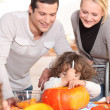 Happy couple and their two girls cooking — Stock Photo #8323110