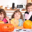Stock Photo: Giggling girls carving pumpkins