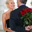 Charming gentlemhiding roses behind his back — Stockfoto #8323138