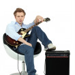 Boy in armchair with guitar and amp — Stock Photo