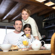 Stock Photo: Young family having breakfast