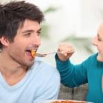 Woman feeding her husband food — Stock Photo #8323486