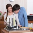 Stock Photo: Couple making crepes.
