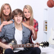 Stock Photo: Three teenagers in bedroom with electric guitar