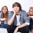Stock Photo: Three teenagers playing computer game
