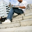 Afro-American man sitting on stairs with laptop — Stock Photo