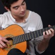 Stock Photo: Young man playing guitar
