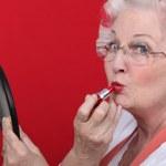 Old lady applying lipstick — Stock Photo