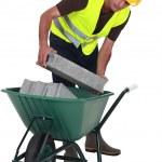 Worker putting cinderblocks in a wheelbarrow — Stock Photo #8325128