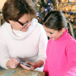 Stock Photo: Grandmother and child playing cards at Christmas