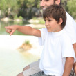 Father and son sitting by a lake — Stock Photo #8325235