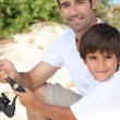 Father and son dishing - Stock Photo