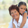Young girl riding piggy-back on her grandmother's back — Stock Photo #8325243