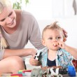 Mother watching son playing with toys — Stock Photo