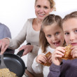 Family cooking pancakes — Stock Photo