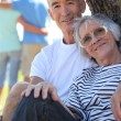 Couple of pensioners posing seated against trunk — Stock Photo