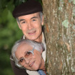 Elderly couple behind tree - Stock Photo