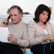 Man on phone and woman knitting at home — Stock Photo