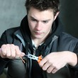 Young electrician using pliers - Stock Photo