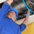 Plumber holding a blue flexible pipe under some air ducts — Stock Photo
