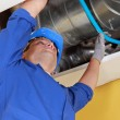 Stock Photo: Plumber holding a blue flexible pipe under some air ducts
