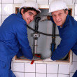Stock Photo: Plumber with young apprentice