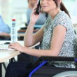 Young woman in a wheelchair at her desk — Stock Photo #8328228