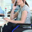 Stock Photo: Young woman in a wheelchair at her desk