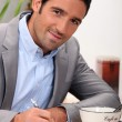 Charming 30 years old man dressed in a grey suit and writing in a cosy plac — Stockfoto